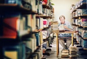 Starszy pan przy stoliku wśród regałów przegląda książki
