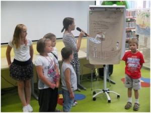 Dzieci na flipcharcie prezentują swoją pracę