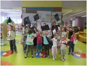 Zdjęcie grupowe dzieci trzymających w górze pirackie bandery