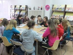 Młodzież siedzi dookoła stołu