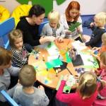 Dzieci i opiekunki przy okrągłym stole