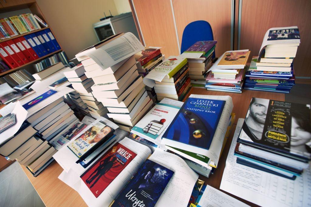 Nowe książki leżą w stosach na stole