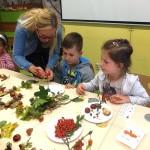Opiekunka pokazuje dziecku jak robić pracę z patykiem