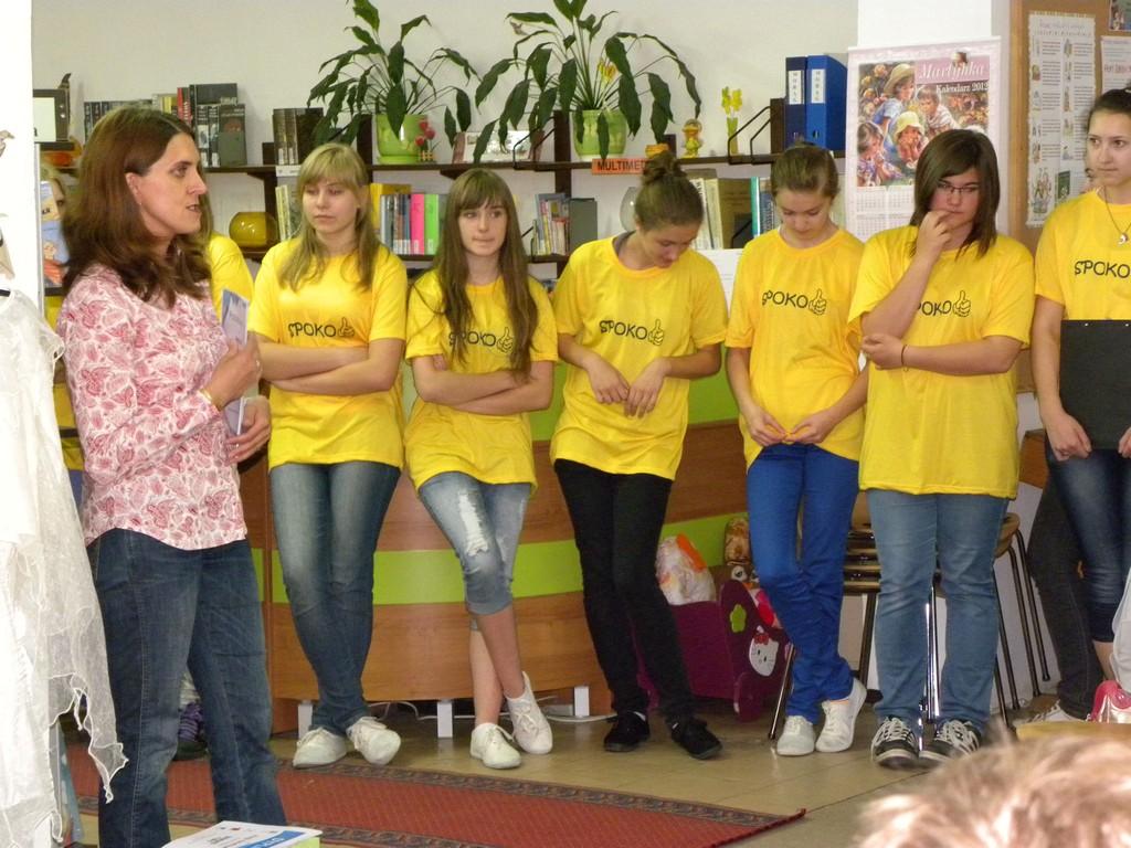 Uczestnicy projektu w żółtych koszulkach z pracownikiem biblioteki