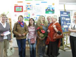 Fotografia grupowa autorki z pracownikami biblioteki i gośćmi