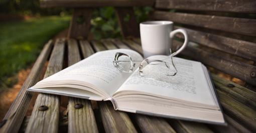 Otwarta książka leży na ławce w parku, na niej leżą okulary, obok jest filiżanka