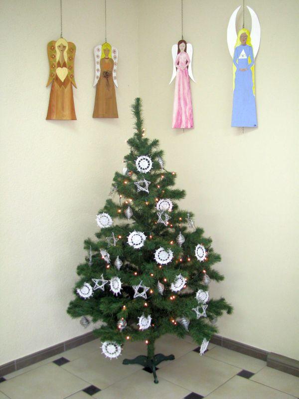 Choinka z koronkowymi ozdobami, nad choinką wiszą drewniane anioły