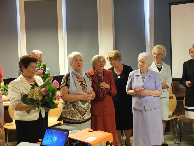 Seniorzy, dwoje trzyma kwiaty