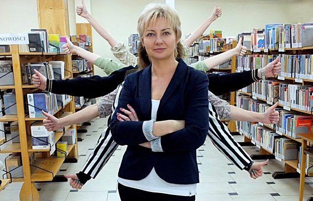 zdjęcie artystyczne, na pierwszym planie dyrektorka biblioteki, za nią ukryci pracownicy z wyciągniętymi rękami trzymającymi kciuki pod różnymi kątami, w tle regały z książkami