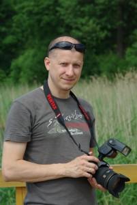 Radosław Obniski trzyma aparat fotograficzny