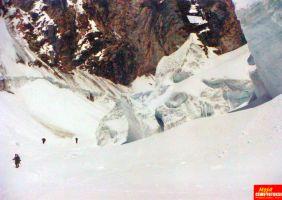 pokrywa śnieżna w górach, w oddali troje alpinistów