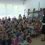 Dzieci siedzą na podłodze i słuchają organizatora