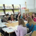Młodzież przy stołach przegląda prasę