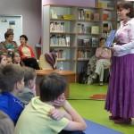 Autorka stoi przed dziećmi i pokazuje swoją książkę