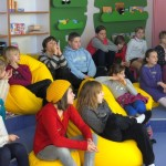 Dzieci siedzą wygodnie na pufach i oglądają prezentację na ekranie