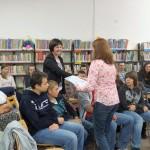 Pracownik biblioteki wręcza dyplom osobie siedzącej wśród gości