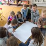 Dzieci zgromadzone wokół dużego arkusza papieru
