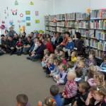 Dzieci siedzą na podłodze i słuchają wypowiedzi organizatora