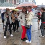 Młodzież pod parasolami kryje się przed deszczem