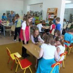 Dzieci przy stole wykonują laurki dla mamy