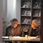 Dwoje aktorów gra siedząc przy stoliku
