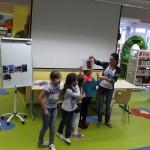 Czwórka dzieci stoi obok bibliotekarki i decyduje gdzie umieścić podaną fotografię na flipcharcie