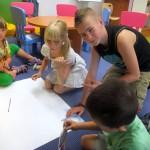 Dzieci siedzą na podłodze i rysują na dużych arkuszach papieru