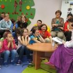 Autorka siedzi przy stoliku i czyta książkę, dzieci słuchają z uwagą