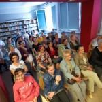 Goście siedząc na krzesłach oglądają przedstawienie