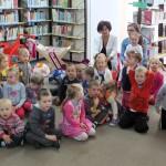 Dzieci z przedszkola siedzą na podłodze, za nimi wychowawczynie