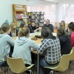 Uczestnicy przy stołach słuchają nauczyciela