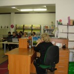 Pracownik przy ladzie biblioteczne, w tle uczestnicy zajęć
