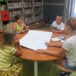 Czworo dzieci siedzi wokół stołu i rysują na dużym arkuszu papieru