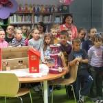 Dzieci przy stole z eksponatami-zabawkami