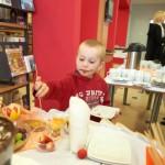 Mały chłopiec bierze owoc ze stołu