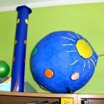 Niebieska kula, na niej słońce i planety, obok niebieska rakieta