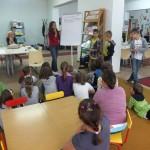 Dzieci słuchają pracownika biblioteki wypisującego informacje na flipcharcie