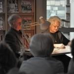 Dwoje aktorów gra siedząc przy stoliku oświetlonym przez lampę
