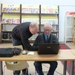 Prowadzący pomaga starszemu panowi przy obsłudze komputera