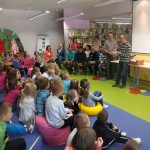 Dzieci siedzą i słuchają wypowiedzi jednego z autorów na temat tworzenia zabawek