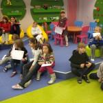 Dzieci siedzą na podłodze i trzymają swoje prace