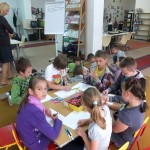 Dzieci siedzą wkoło stolika i rysują na kartkach