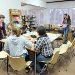 Uczestnicy pracują przy stole nad relacją dziennikarską