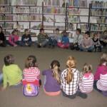 Dzieci siedzą w kółeczku na podłodze