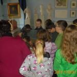 Dzieci w muzeum słuchają kustosza