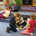 Dzieci siedzą w grupkach i przyklejają obrazki do kartki