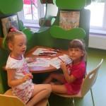 Dwie dziewczynki kolorują wydrukowany statek na kartkach