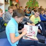 Dzieci siedzą i przeglądają książki