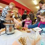 Dzieci i dyrektor biblioteki biorą smakołyki ze stołu, na stole fontanna gorącej czekolady