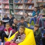 Dzieci w skupieniu siedzą na podłodze